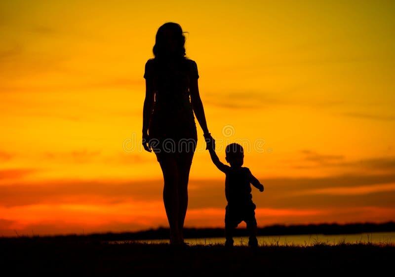 Attraktiv barnmoder på gå med barnet fotografering för bildbyråer