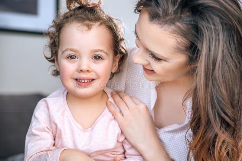 Attraktiv barnmoder som kramar hennes älskade barn royaltyfri foto