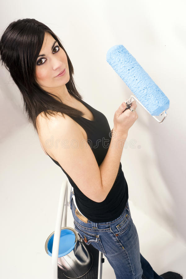 Attraktiv behändig kvinna som använder projekt för målarfärg för blått för målarfärgrulle royaltyfria foton