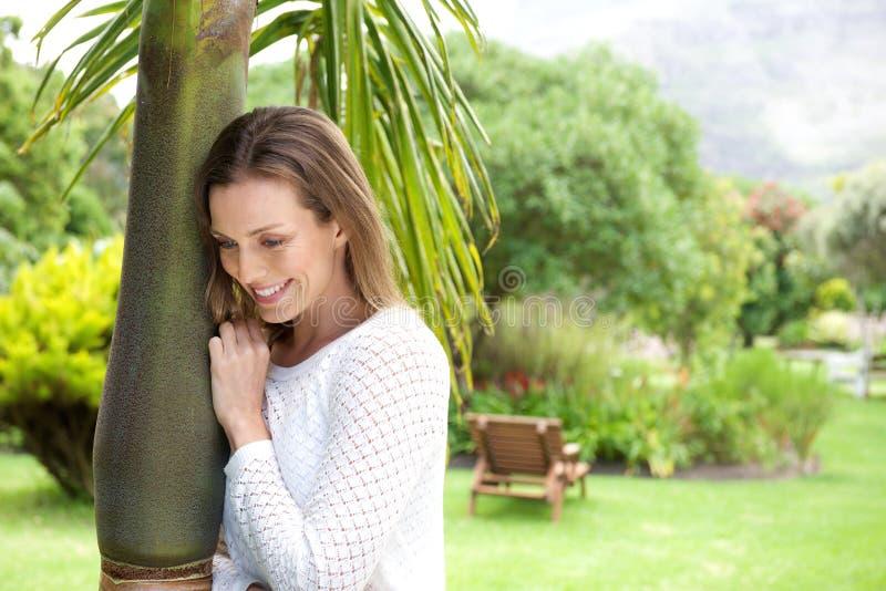 Attraktiv benägenhet för äldre kvinna mot träd och att le fotografering för bildbyråer