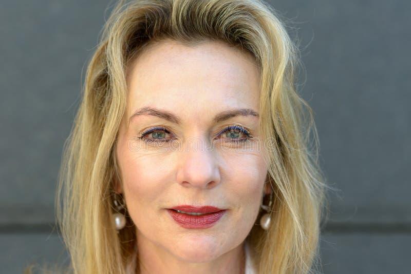 Attraktiv blått synad bärande makeup för blond kvinna arkivfoton