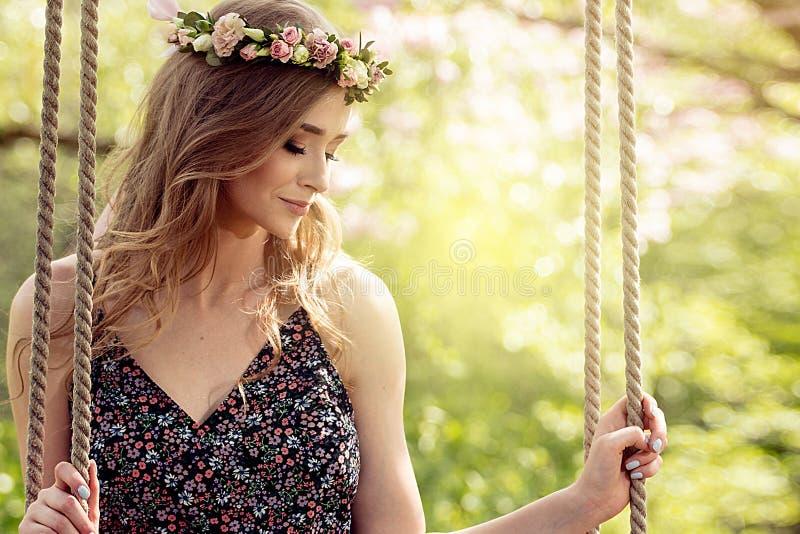 Attraktiv blond flicka i blommande trädgård royaltyfri fotografi