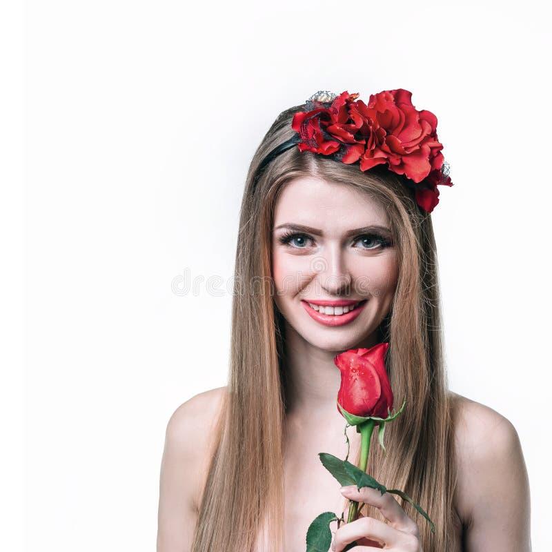 Attraktiv blond flicka med den röda rosen Isolerat på vit arkivfoto