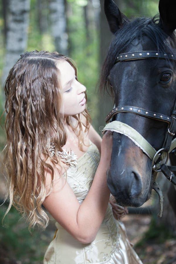 Attraktiv blond flicka med henne häst. arkivfoto