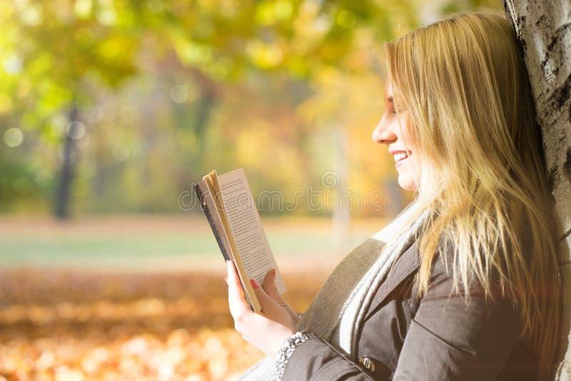 Attraktiv blond flicka som tycker om en bok i en parkera royaltyfri foto