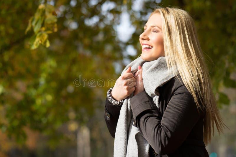 Attraktiv blond flicka som tycker om en parkera arkivfoto