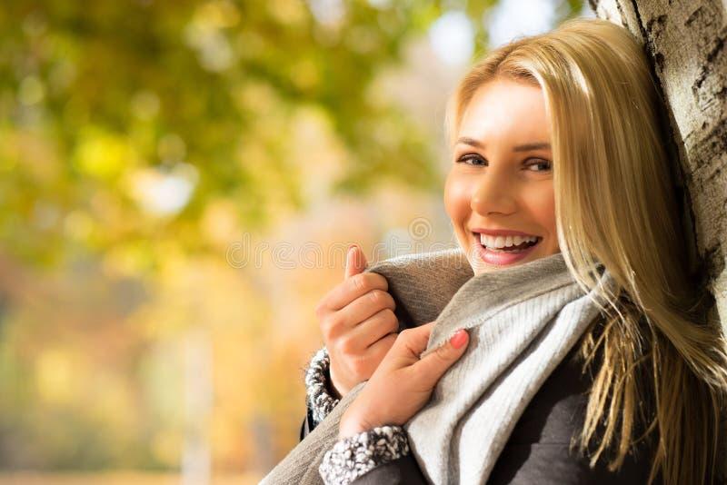 Attraktiv blond flicka som tycker om en parkera royaltyfri foto