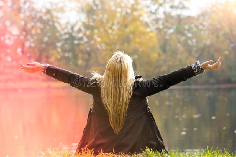 Attraktiv blond flicka som tycker om en parkera fotografering för bildbyråer