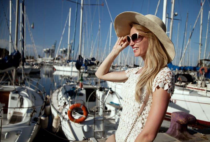 Attraktiv blond kvinna i hamn royaltyfri foto
