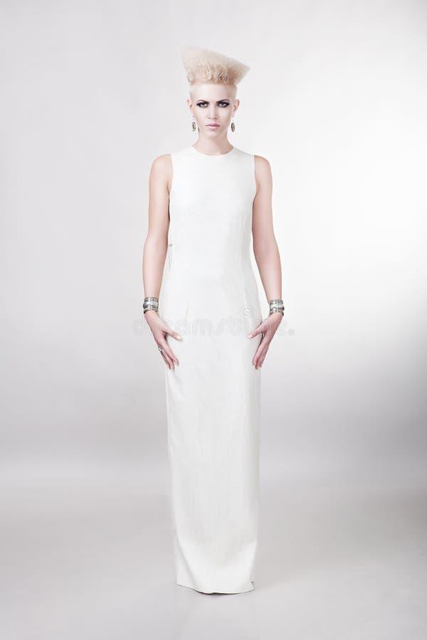 Attraktiv blond kvinna i lång vit klänning med idérikt hår arkivfoton