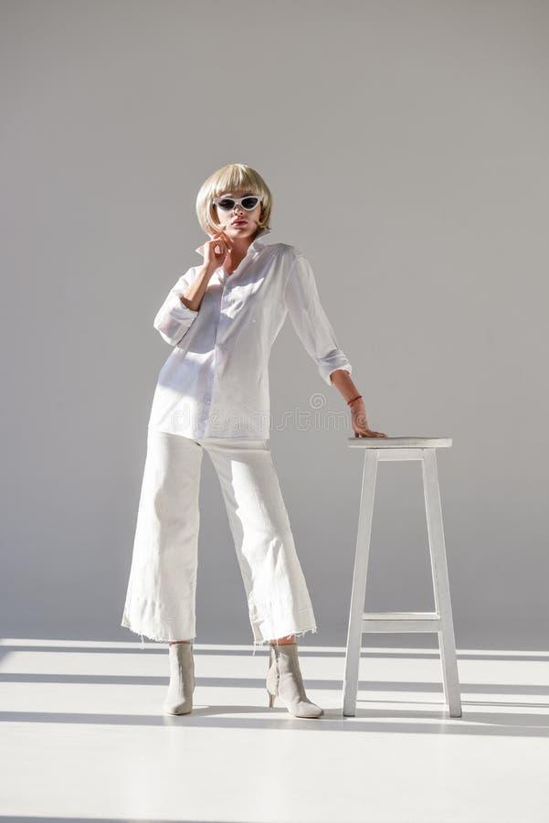 attraktiv blond kvinna i solglasögon och den trendiga vita dräkten som lutar på stol arkivfoto