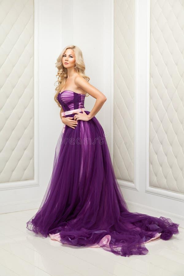 Attraktiv blond kvinna i trendig purpurfärgad klassisk aftonklänning med makeup och långt krabbt frisyranseende och att posera nä arkivfoton