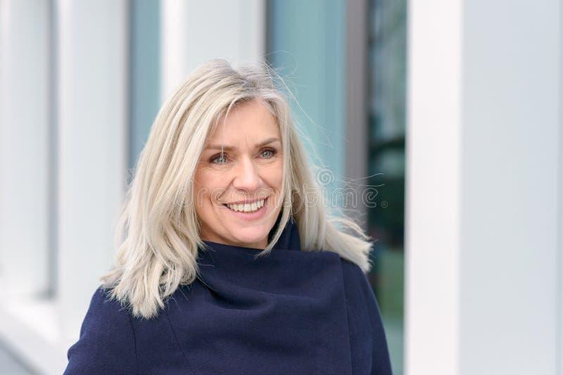 Attraktiv blond kvinna med ett varmt lyckligt leende arkivfoto