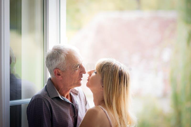 Attraktiv blond kvinna som kramar den stiliga höga mannen och ser honom med förälskelse och passion i henne ögon Par med ålder arkivfoton