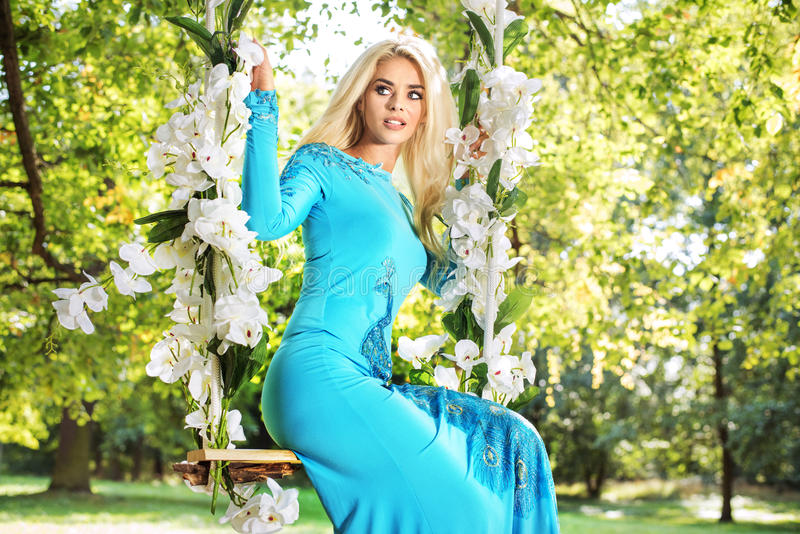 Attraktiv blond skönhet på en blommagunga i en parkera royaltyfri fotografi