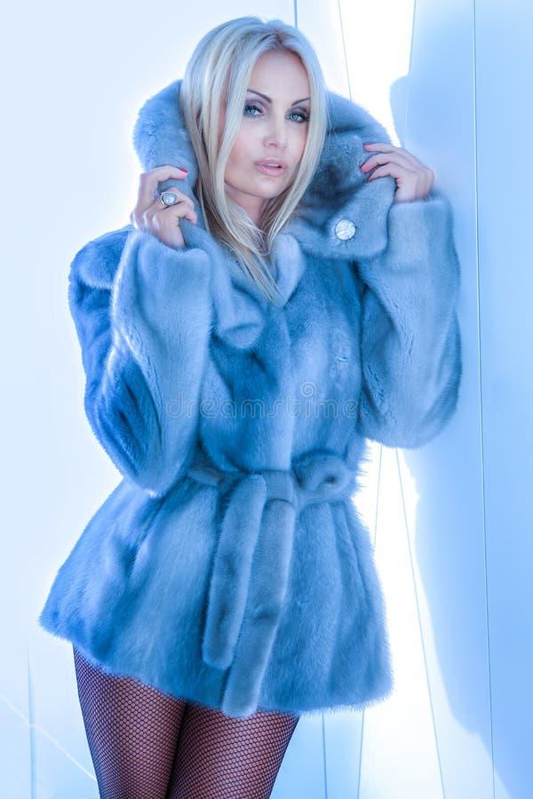 Attraktiv blond skönhet som poserar bärande päls. arkivfoton
