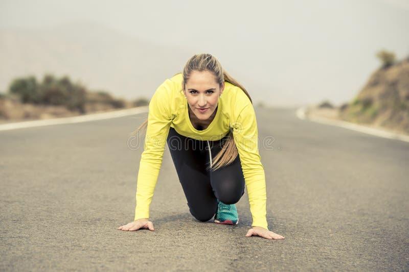 Attraktiv blond sportkvinna som är klar att starta köra start för övningsutbildningslopp på landskap för berg för asfaltväg royaltyfri bild