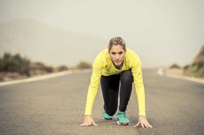 Attraktiv blond sportkvinna som är klar att starta köra start för övningsutbildningslopp på landskap för berg för asfaltväg arkivfoton