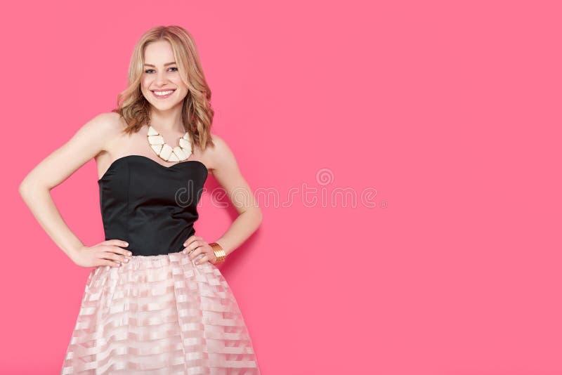 Attraktiv blond ung kvinna i elegant partiklänning och guld- smycken Flicka som poserar på en bakgrund för pastellfärgade rosa fä royaltyfria bilder