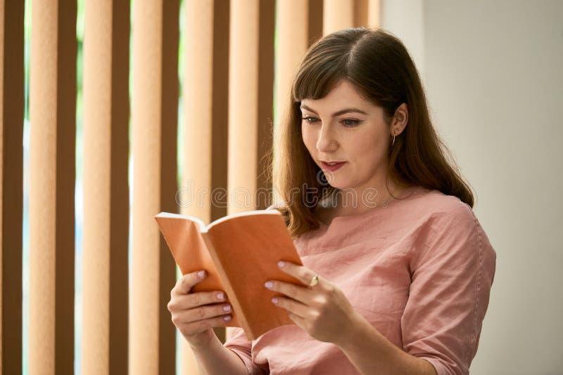 attraktiv bokavläsningskvinna fotografering för bildbyråer