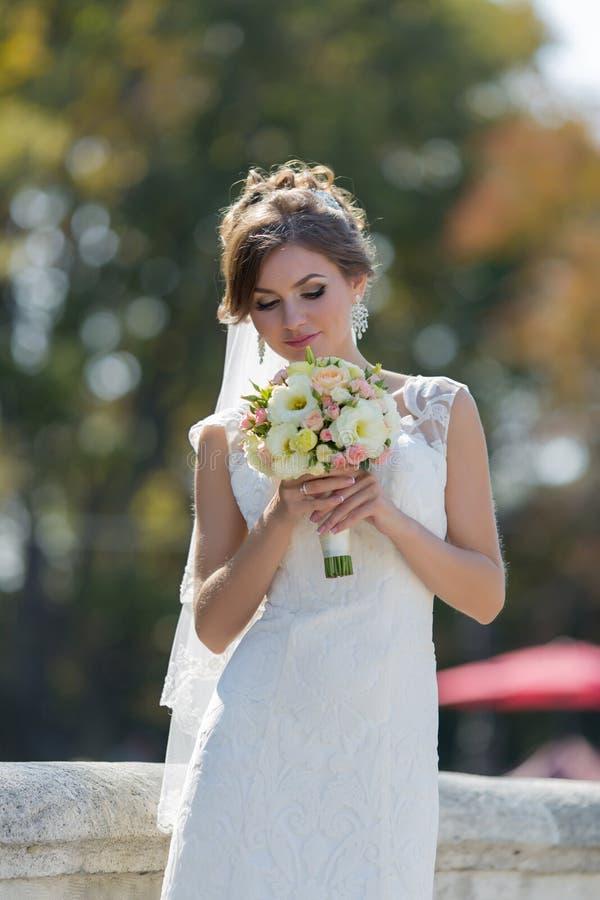 Attraktiv brud med brud- liten bukett som poserar på öppen luft royaltyfria foton