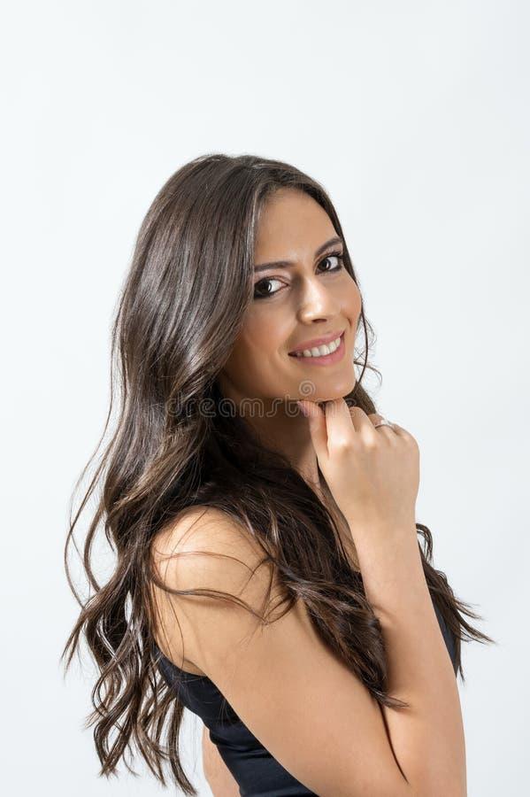 Attraktiv brunbränd lång modell för hårkvinnaskönhet som poserar och ler royaltyfri bild