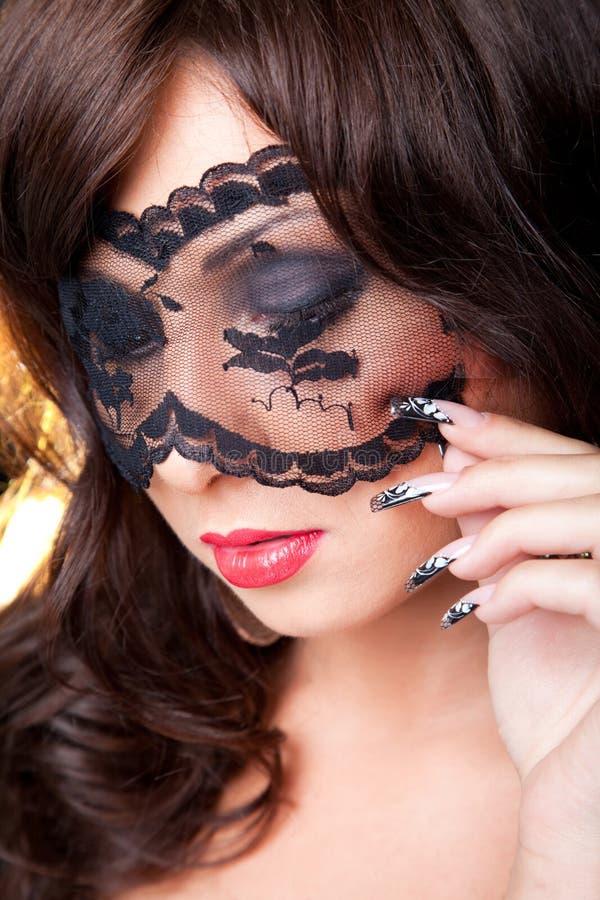 Attraktiv brunettflicka med den lacy maskeringen på henne öga fotografering för bildbyråer