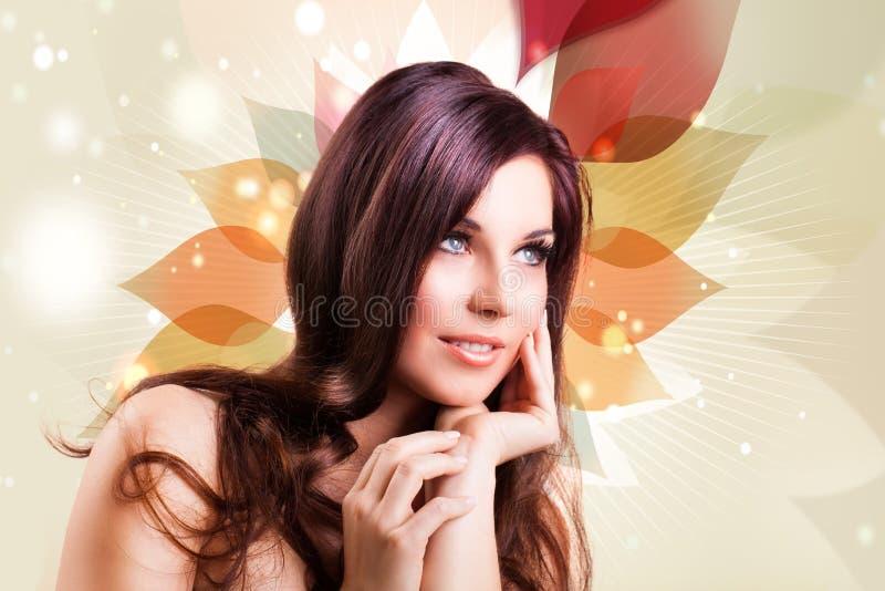 Attraktiv brunettkvinna framme av en abstrakt bakgrund arkivfoto