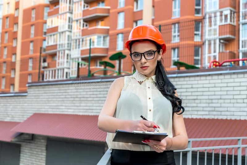 Attraktiv brunettkvinna som ber?knar n?got p? konstruktionsplats arkivbild