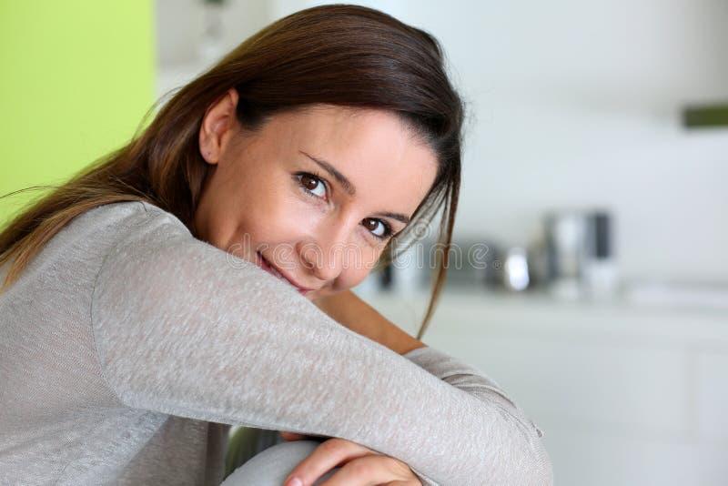 Attraktiv brunettkvinna som hemma sitter royaltyfria foton