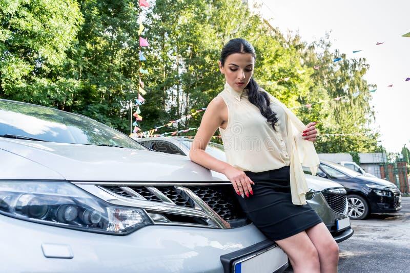 Attraktiv brunettkvinna som poserar nära den nya bilen royaltyfri foto