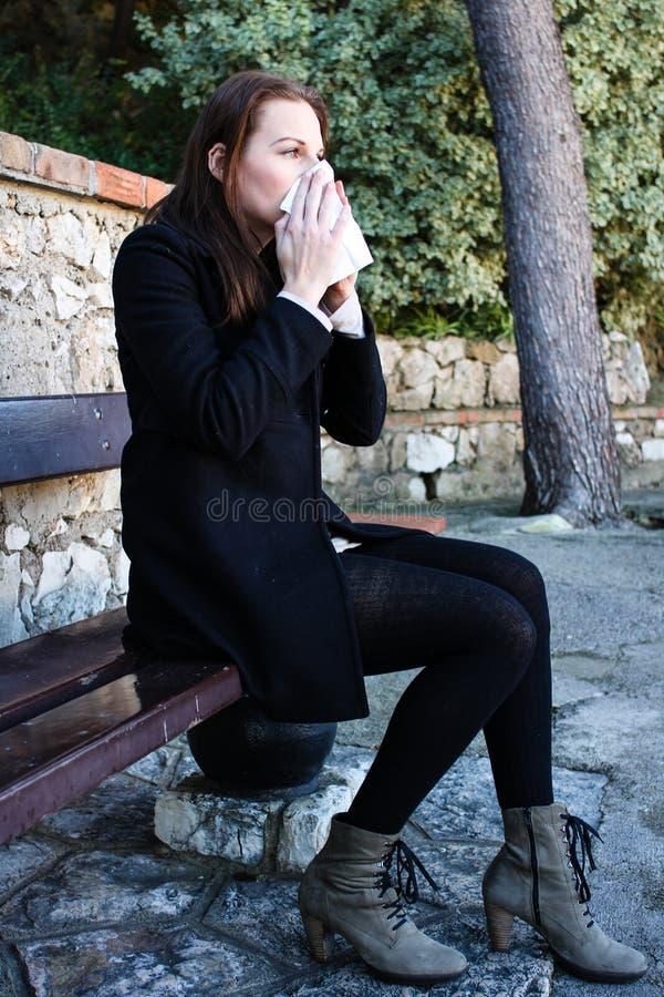 Attraktiv brunettkvinna som slår henne näsa royaltyfria bilder