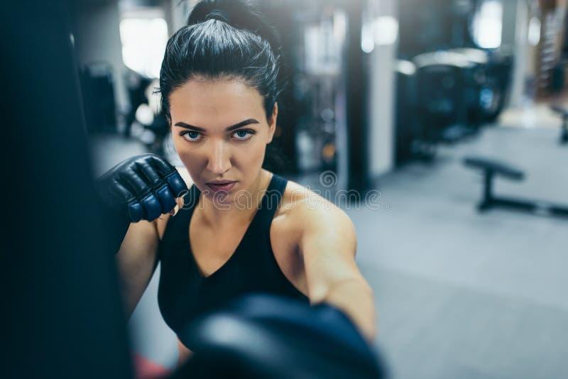 Attraktiv brunettkvinnainstruktör som stansar en påse med kickboxing handskar i idrottshallen och ser främre på kameran Sport kon royaltyfri bild