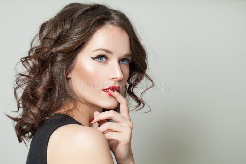 Attraktiv brunettmodellstående Härlig kvinna med makeup och den bruna ståenden för lockigt hår royaltyfria foton