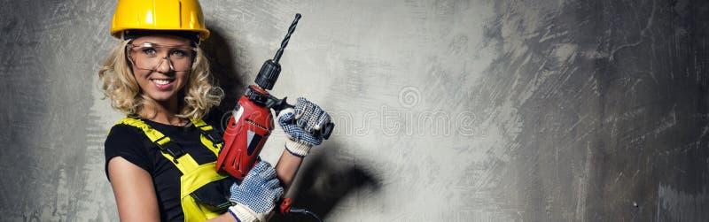 Attraktiv byggmästarekvinna med drillborren horisontalbild royaltyfri foto