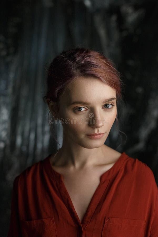 Attraktiv caucasian flicka i röd skjorta med den djupa urringningen och öppna nyckelben som står mot suddig tygbakgrund arkivfoton