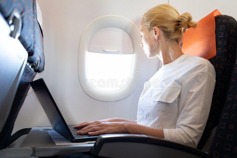Attraktiv caucasian kvinnlig passagerare som ser till och med det vanliga fönstret, medan arbeta på modernt använda för bärbar da royaltyfria foton