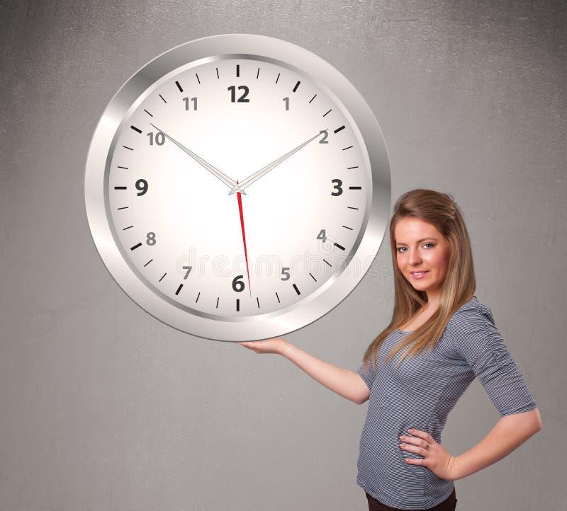 Attraktiv dam som rymmer en enorm klocka royaltyfri bild
