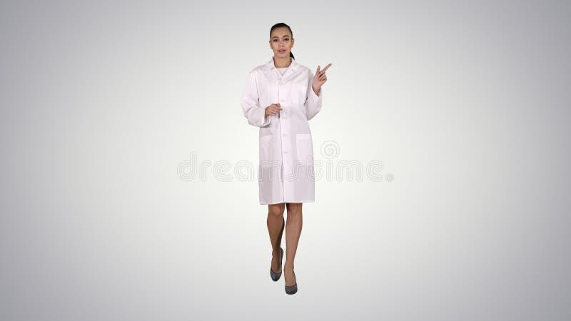 Attraktiv doktor som pekar till sidan som framl?gger produkten p? lutningbakgrund arkivfoton