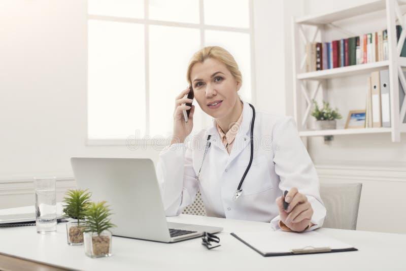 Attraktiv doktor som talar på telefonen med patienten royaltyfri bild