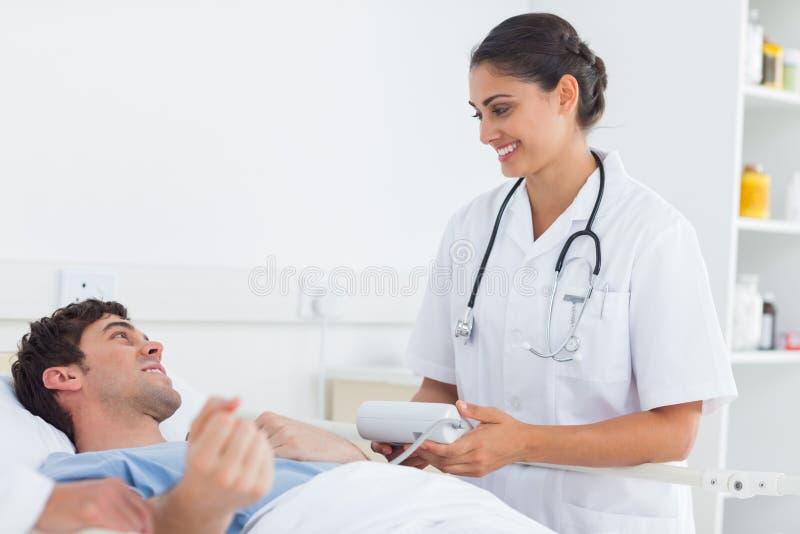 Attraktiv doktor som tar blodtrycket av en patient arkivfoton