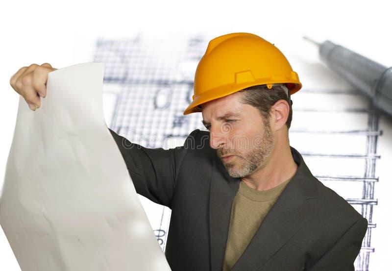 Attraktiv effektiv och säker arkitektman i byggmästarehjälm som kontrollerar ritningar för byggnadskonstruktion på design royaltyfri fotografi
