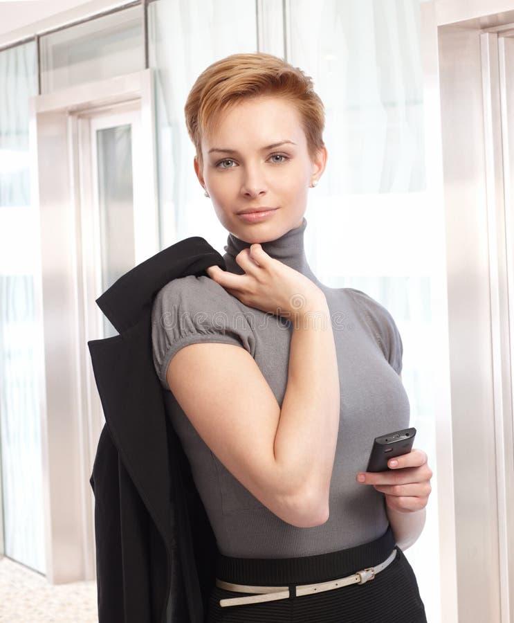 Attraktiv elegant affärskvinna med mobiltelefonen fotografering för bildbyråer