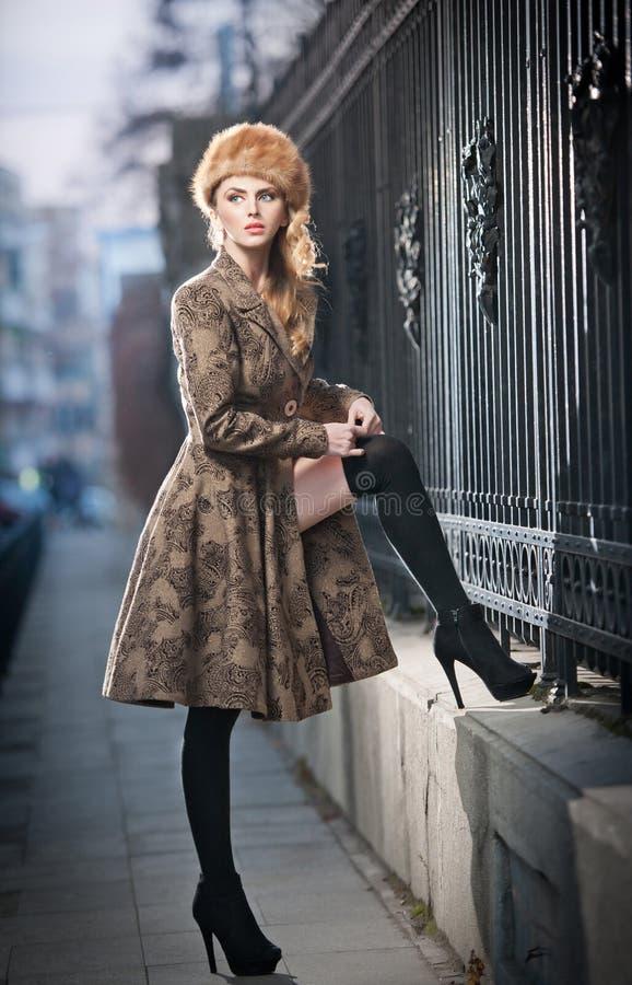 Attraktiv elegant blond ung kvinna som bär en dräkt med rysk påverkan i stads- modeskott. Härlig trendig flicka arkivfoto