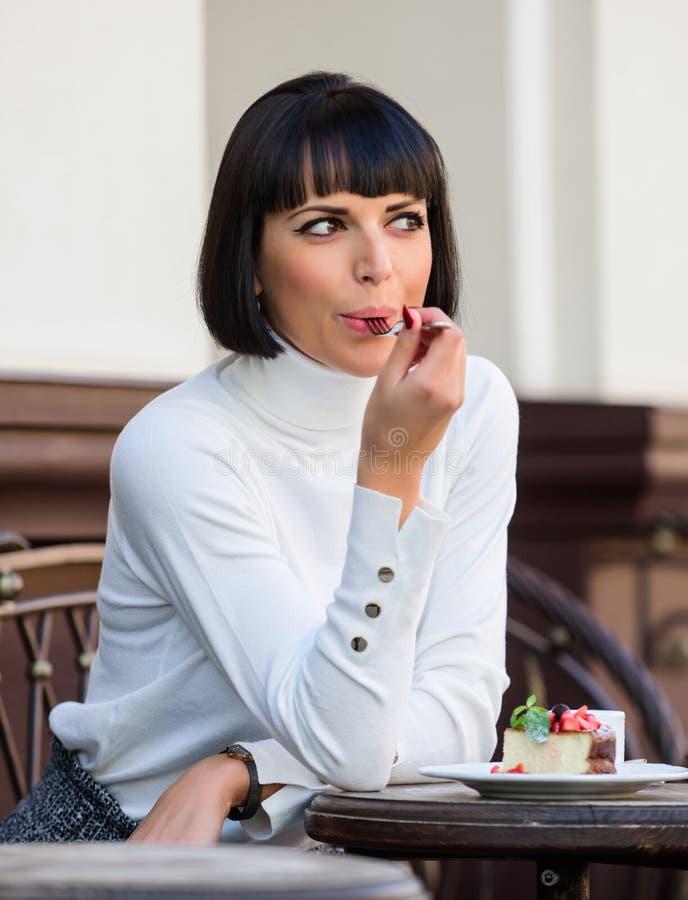 Attraktiv elegant brunett f?r kvinna att ?ta gourmet- bakgrund f?r kakakaf?terrass Gourmet- begrepp Angen?m tid och arkivfoton