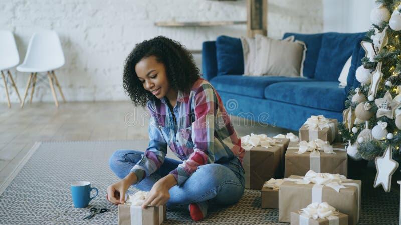 Attraktiv för flickaemballage för blandat lopp ask för gåva nära julgranen hemma royaltyfri foto