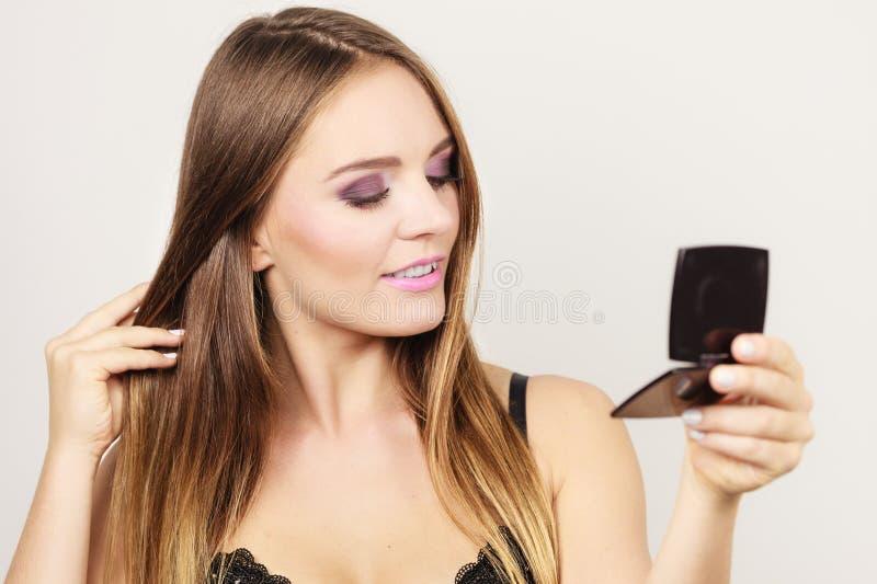 Attraktiv flicka för kvinna som ser i spegel royaltyfri foto