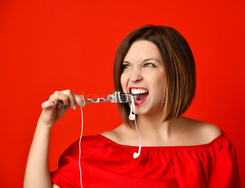 Attraktiv flicka i den röda klänningen som rymmer en gaffel i händer på headphoneproppen Förberett att äta arkivbild