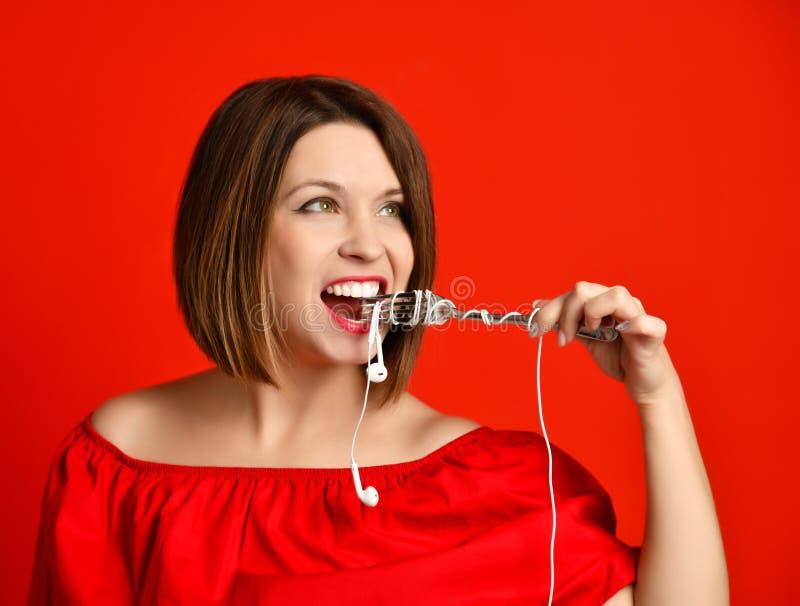 Attraktiv flicka i den röda klänningen som rymmer en gaffel i händer på headphoneproppen Förberett att äta royaltyfri fotografi