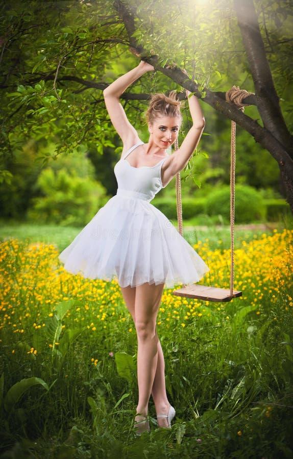 Attraktiv flicka i den vita korta klänningen som poserar nära en trädgunga med en blommig äng i bakgrund blont kvinnabarn royaltyfri fotografi